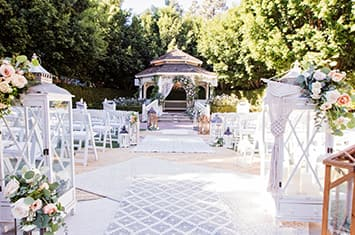 An outdoor area set up for a wedding with chairs on either side of an aisle and a gazebo decorated with flowers at the end of the aisle