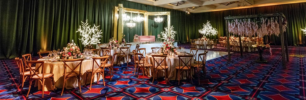 Round tables and chairs set up near a dance floor in a ballroom at the Disneyland hotel