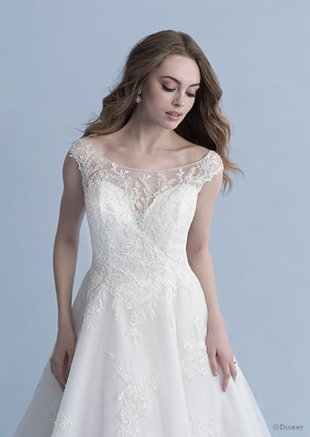 A woman glances down at the Snow White wedding gown from the 2020 Disney Fairy Tale Weddings Collection that she is wearing