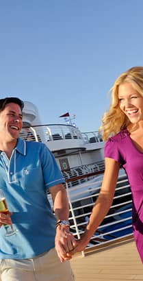 A man and woman hold hands on the deck of a cruise ship