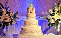 A wedding cake with a Cinderella Castle themed cake topper