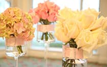 Three bouquets of flowers in glass vases