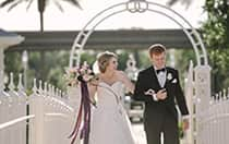 A happy bride and groom walk across a bridge