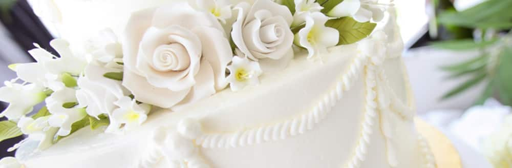 A wedding cake topped with fondant roses and flowers