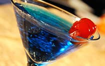 A martini glass filled with a cocktail topped with a cherry
