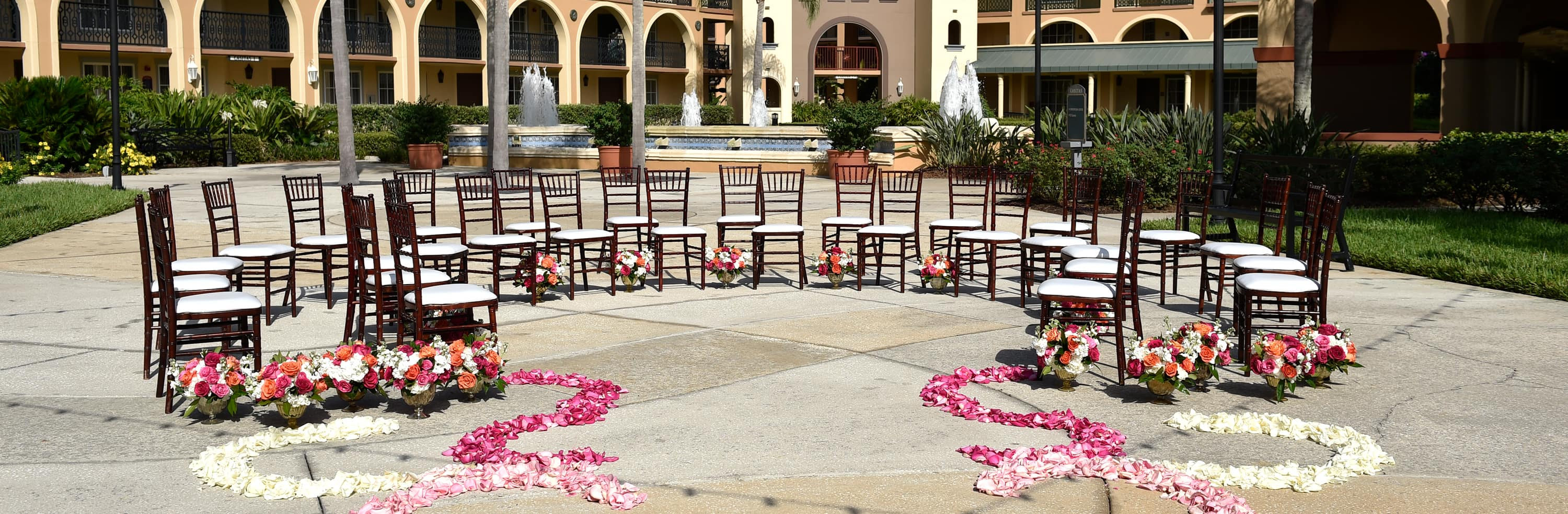 Rose petals lead to a group of chairs arranged in a semi circle on a courtyard with a large water fountain