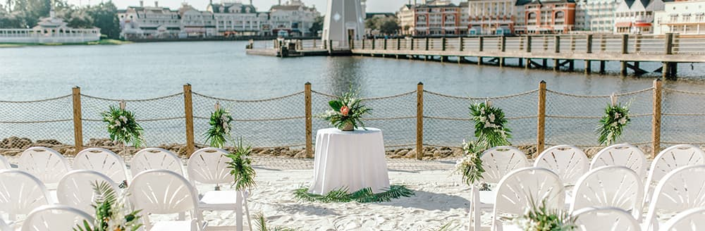 A round table on a beach in front of a lighthouse and Disney's BoardWalk