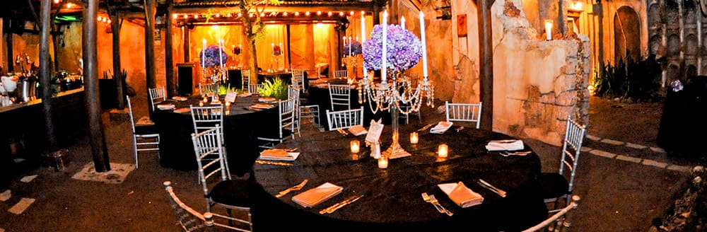 Round tables with tall candlesticks as centerpieces