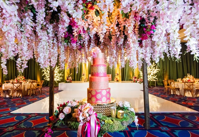 A 4 layer cake sits on a circular table under a canopy of hanging flowers in a room with a dance floor