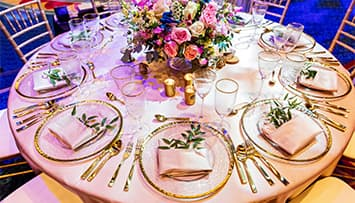 A circular table with a large floral center piece and 10 ornate place settings