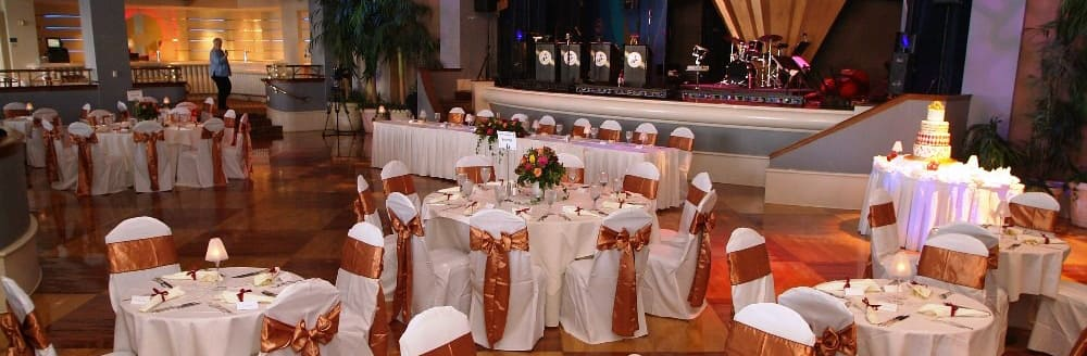 A ballroom with a stage for a live band, tables topped with floral bouquets and dinnerware, chairs decorated with ribbon backs and a wedding cake