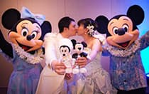 Mickey and Minnie celebrate as a bride and groom kiss