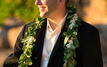 A man wearing a lei around his suit
