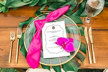 A place setting rests on tropical leaves and consists of 2 forks, 2 knives and a clear plate with an Aulani Resort menu, napkin and flower on top