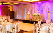 Several round tables, a small dance floor and a cake table