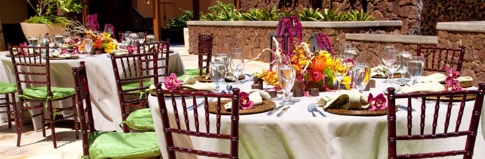 Two round tables surrounded by chairs on an outside patio