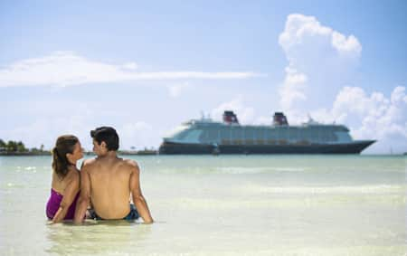 A man and a woman in bathing suits sit on the beach with a Disney Cruise Line ship in the background