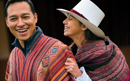 A man and a woman wearing traditional outfits share a laugh