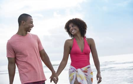 A man and a woman hold hands as they walk along the beach at Disney's Hilton Head Resort