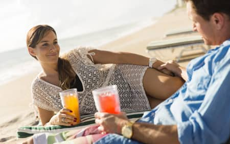 A woman and a man relax on chaise lounges beachside while enjoying tropical drinks