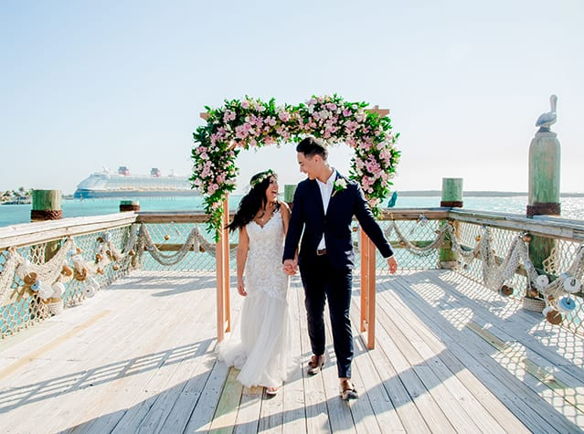 A bride and groom smile at each other while standing on a seaside lookout point