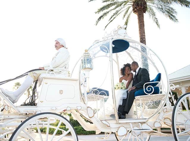 A bride and groom smile at each other while sitting inside Cinderella's Crystal Coach