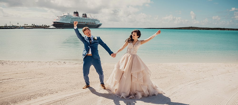 A man in a suit and woman in a wedding dress stand on a sandy beach and hold hands while raising their arms in the air with the ocean and a Disney Cruise Line ship in the background