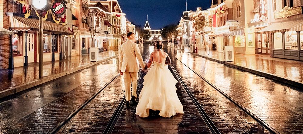 A bride and a groom walk down an empty Main Street, U S A in Magic Kingdom park at Walt Disney World Resort lit up at night
