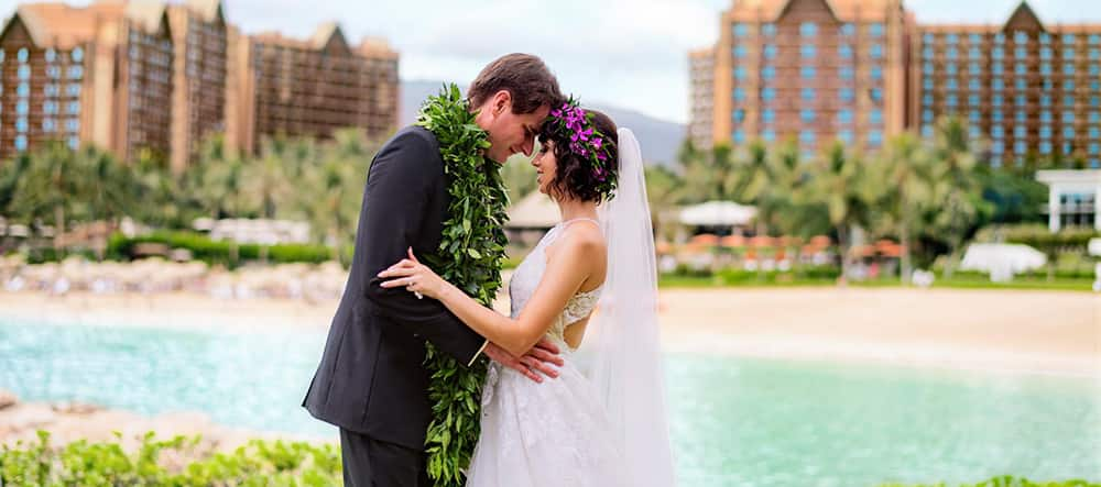 A man and a woman, draped in a Hawaiian lei and headdress, hold each other and stand nose to nose with Aulani Resort in the background