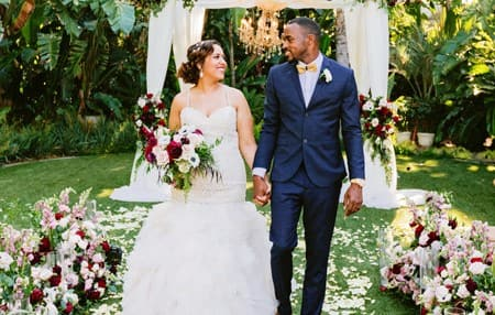 Couple holding hands walking down an isle outside covered with flower petals.