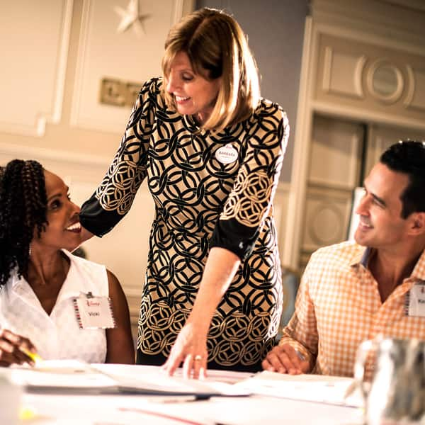 A smiling Disney Institute facilitator talks with one of the attendees at a table