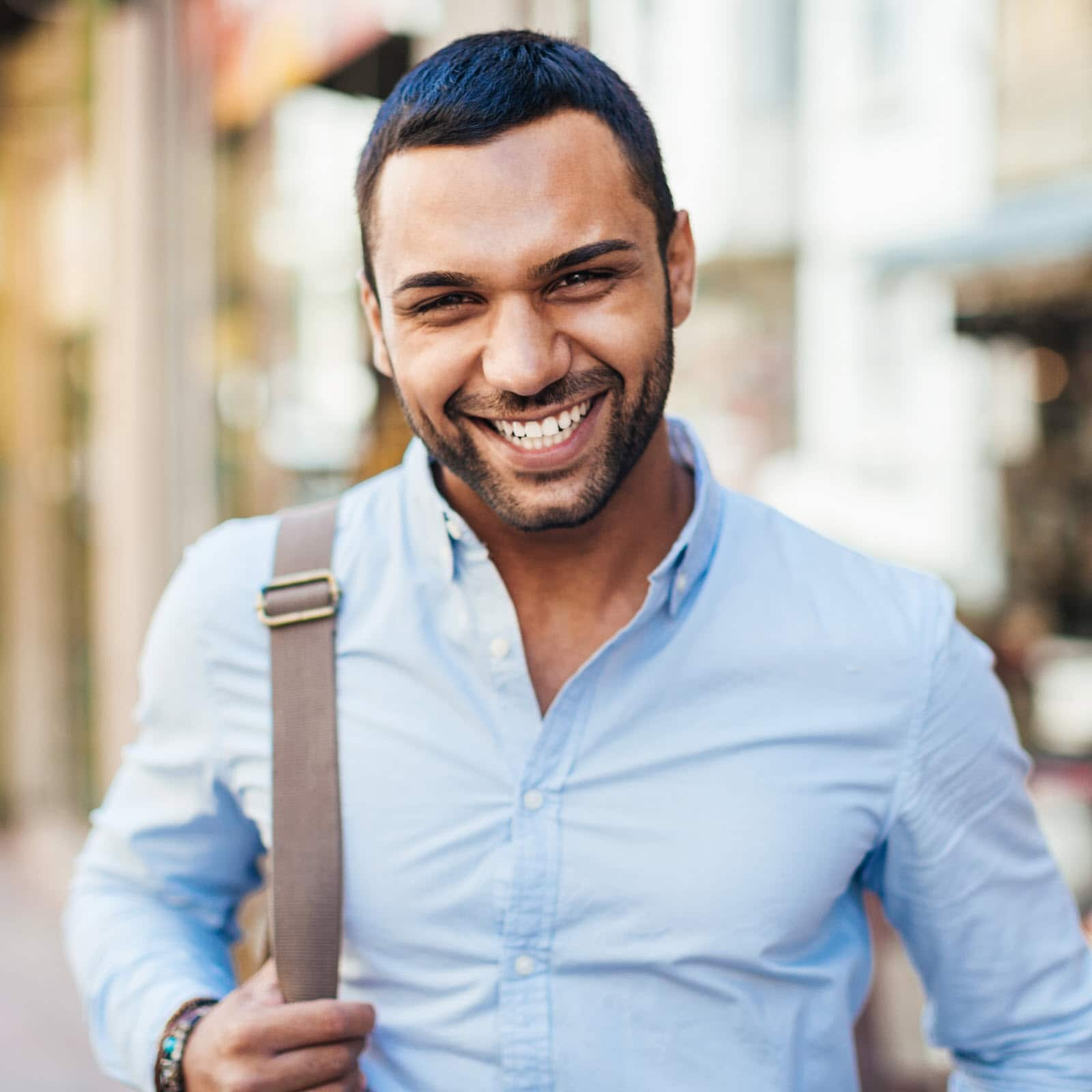 A youthful man carrying a shoulder bag smiles broadly