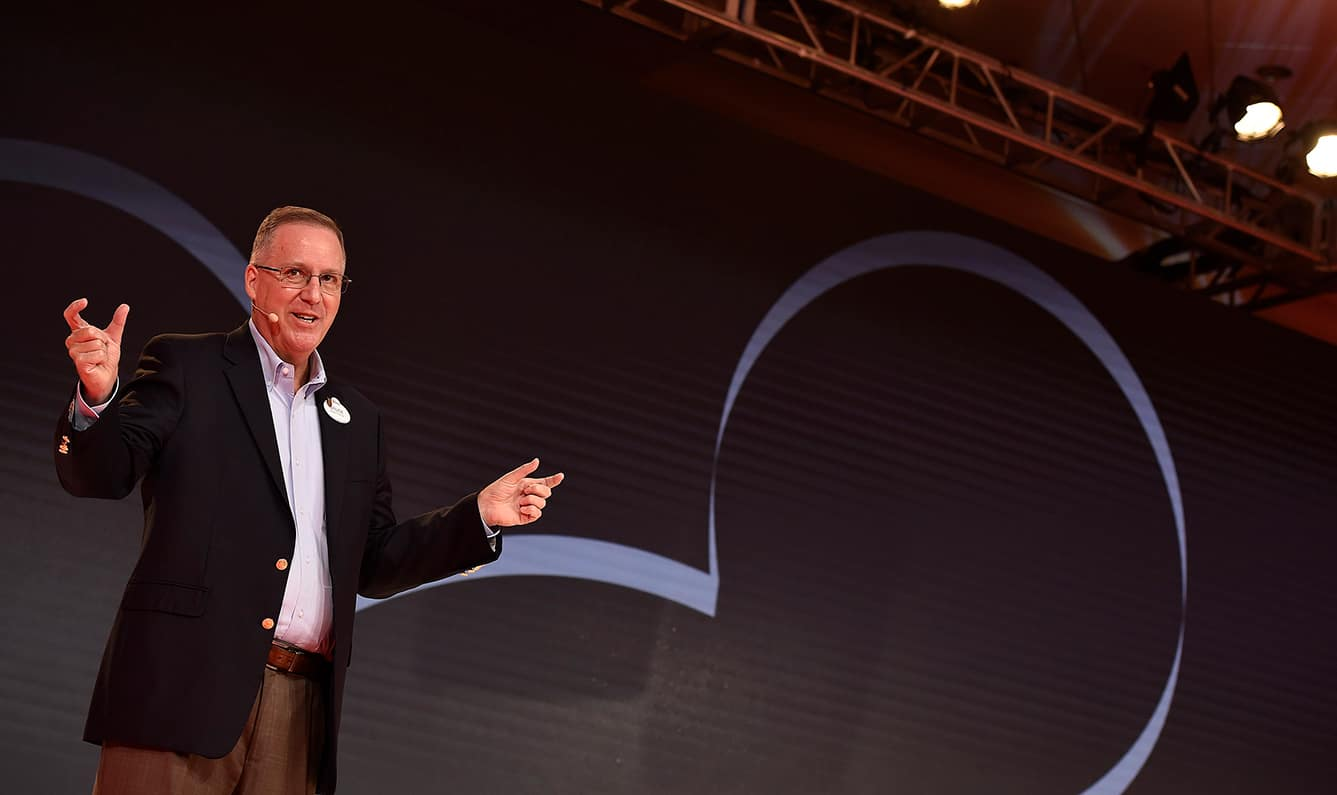 A Disney speaker on a stage gesticulates with his hands to help convey his thoughts