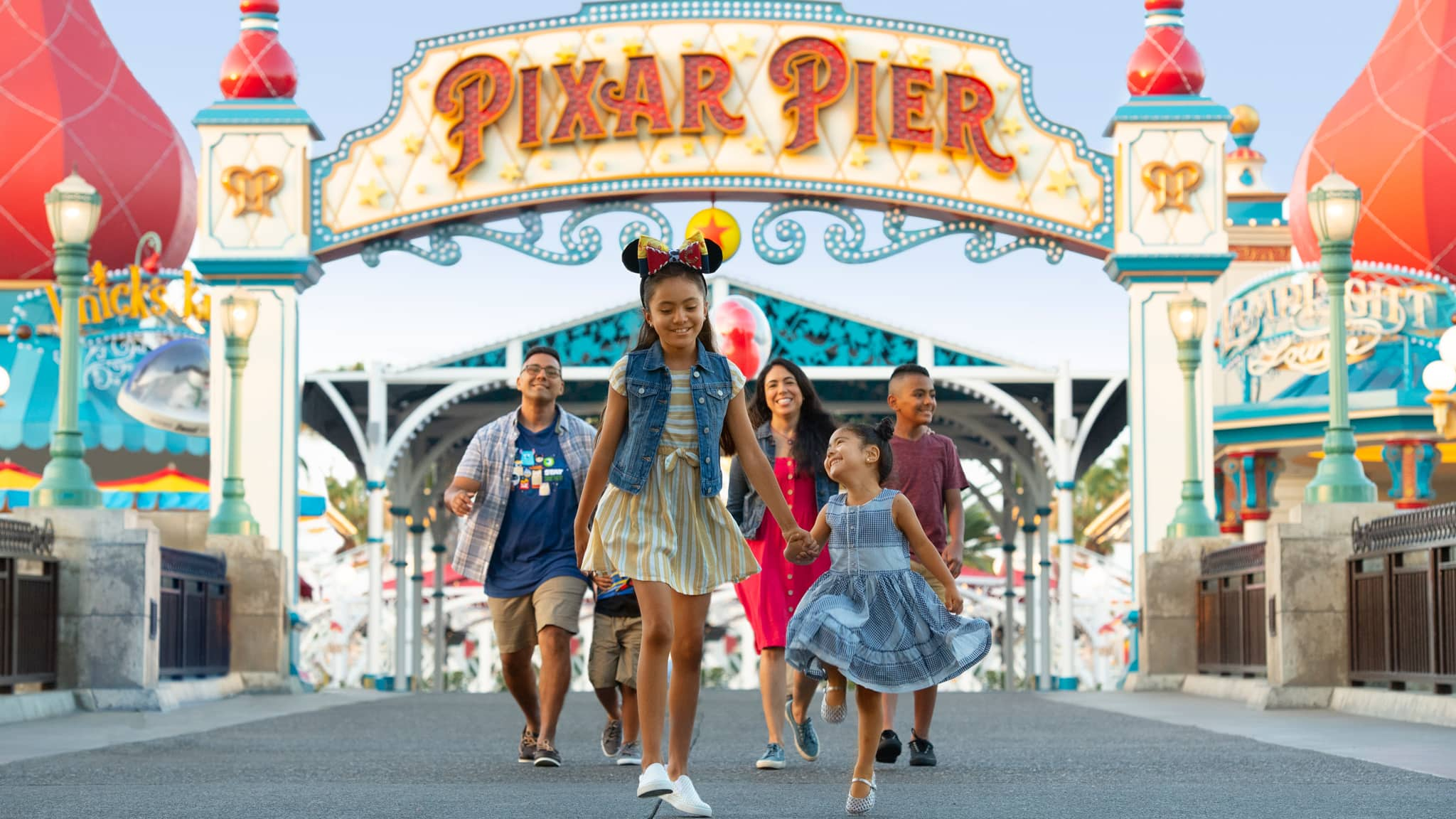 A family of six strolls under the Pixar Pier archway at Disney California Adventure Park