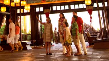 A family wearing leis standing in a Resort lobby
