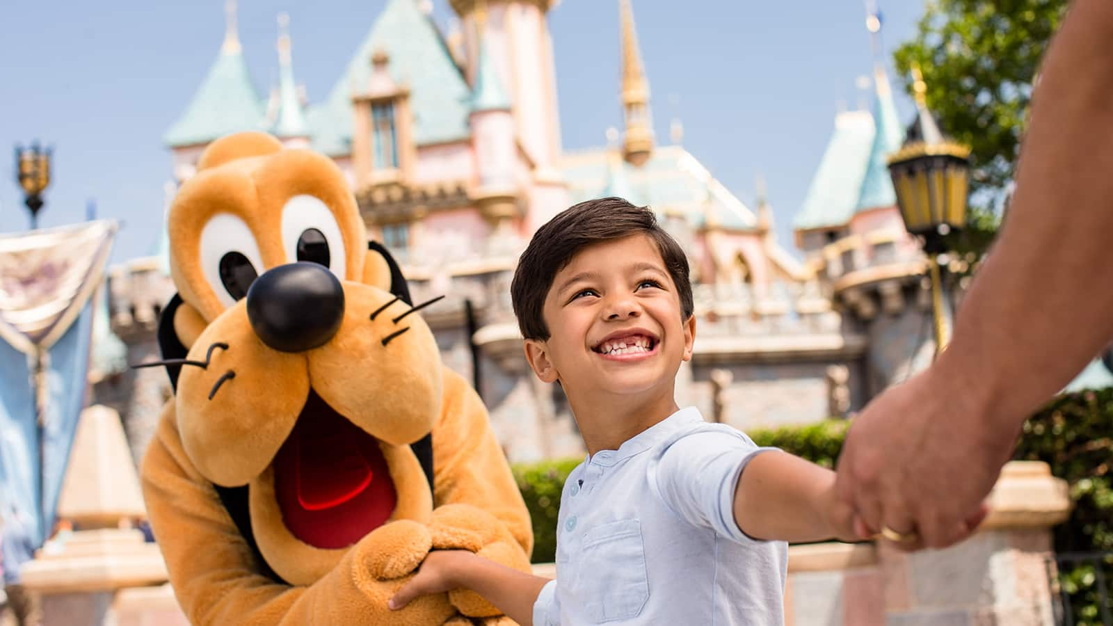 Pluto with boy in front of Sleeping Beauty's Castle