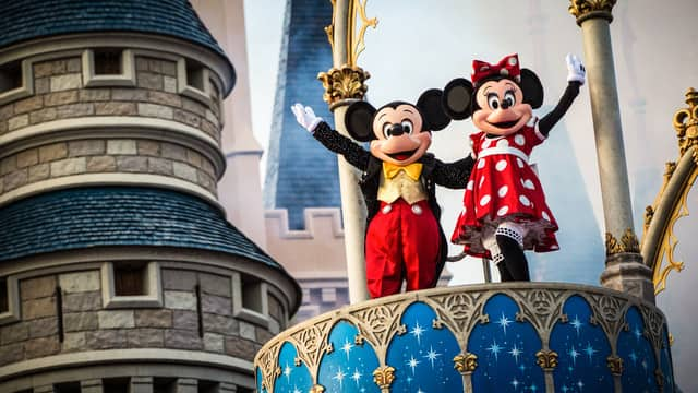 Mickey and Minnie wave from a perch at Cinderella Castle
