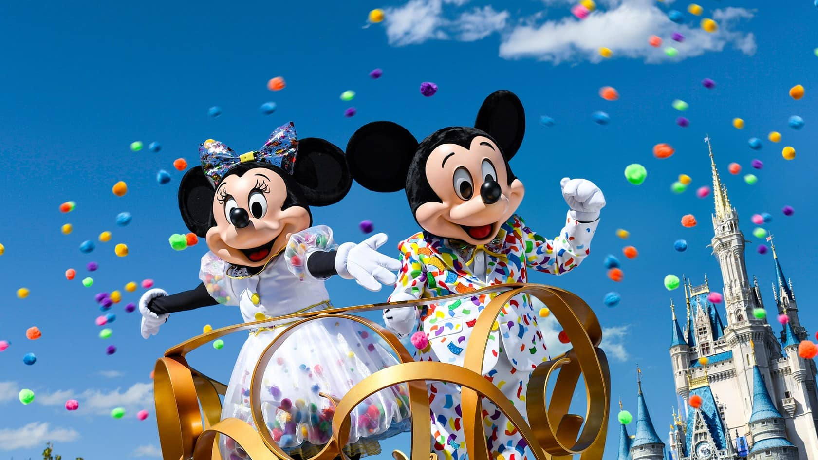 Mickey and Minnie Mouse standing atop a parade float at Magic Kingdom park