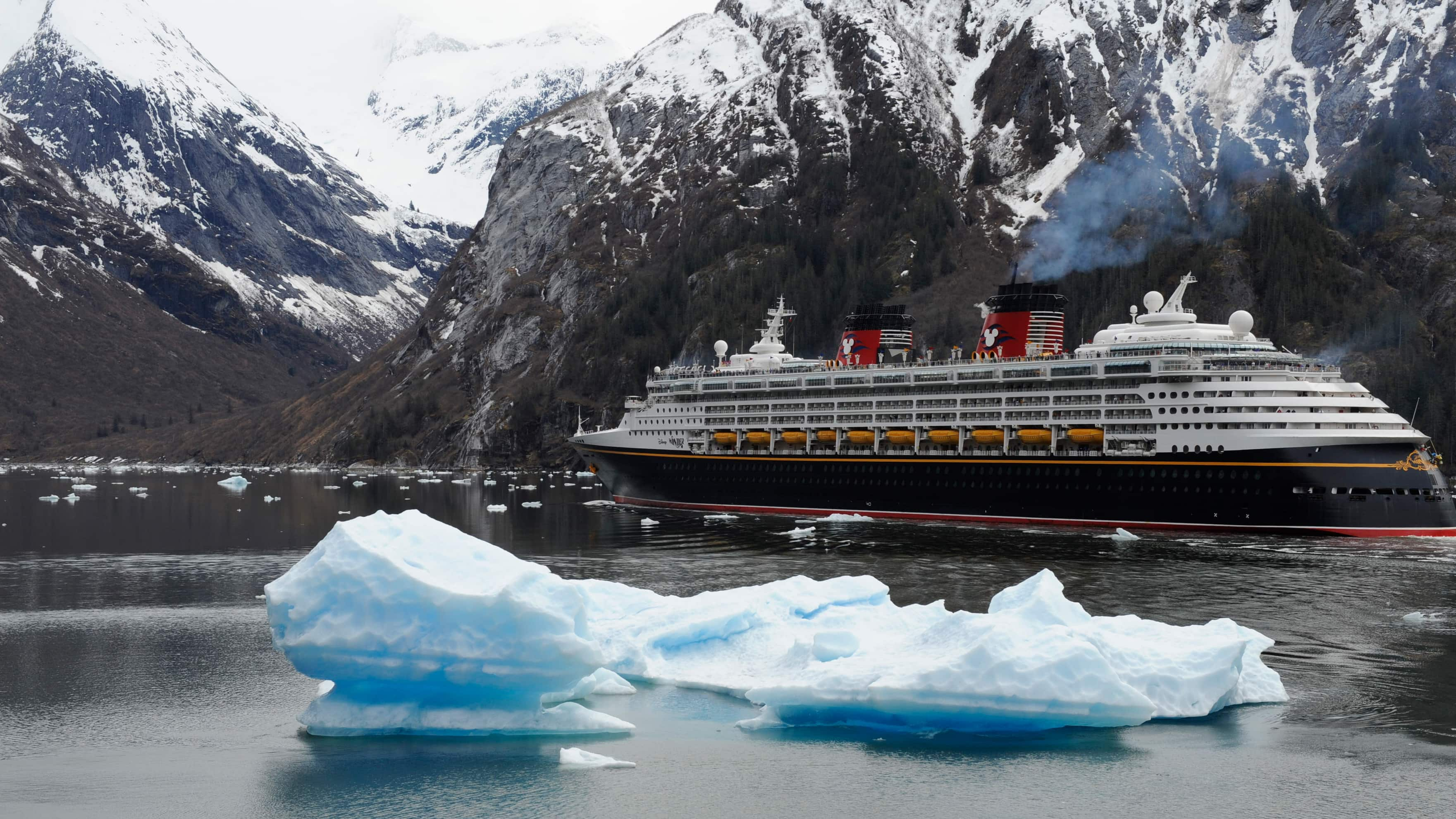 A Disney Cruise Line ship sails by snow capped mountains in Alaska