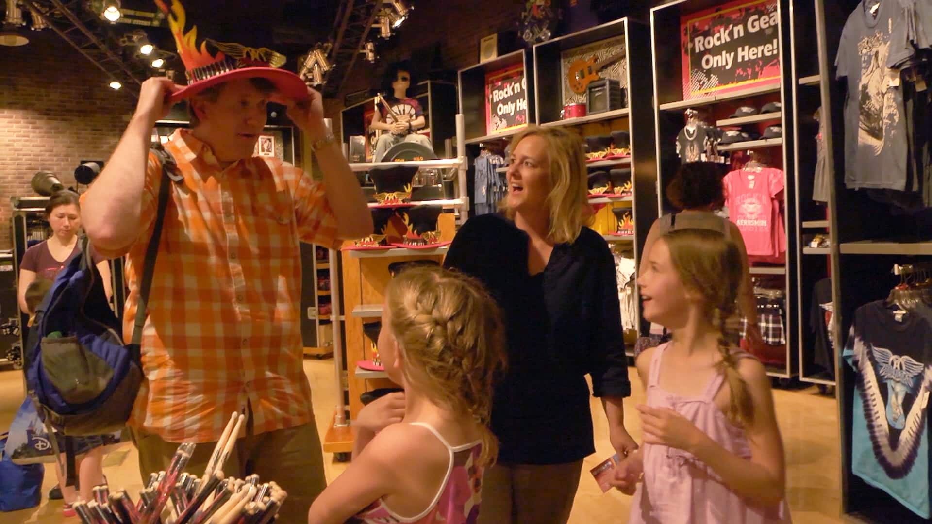 2 girls and their mother laugh as their father puts on a flamboyant hat in a gift shop