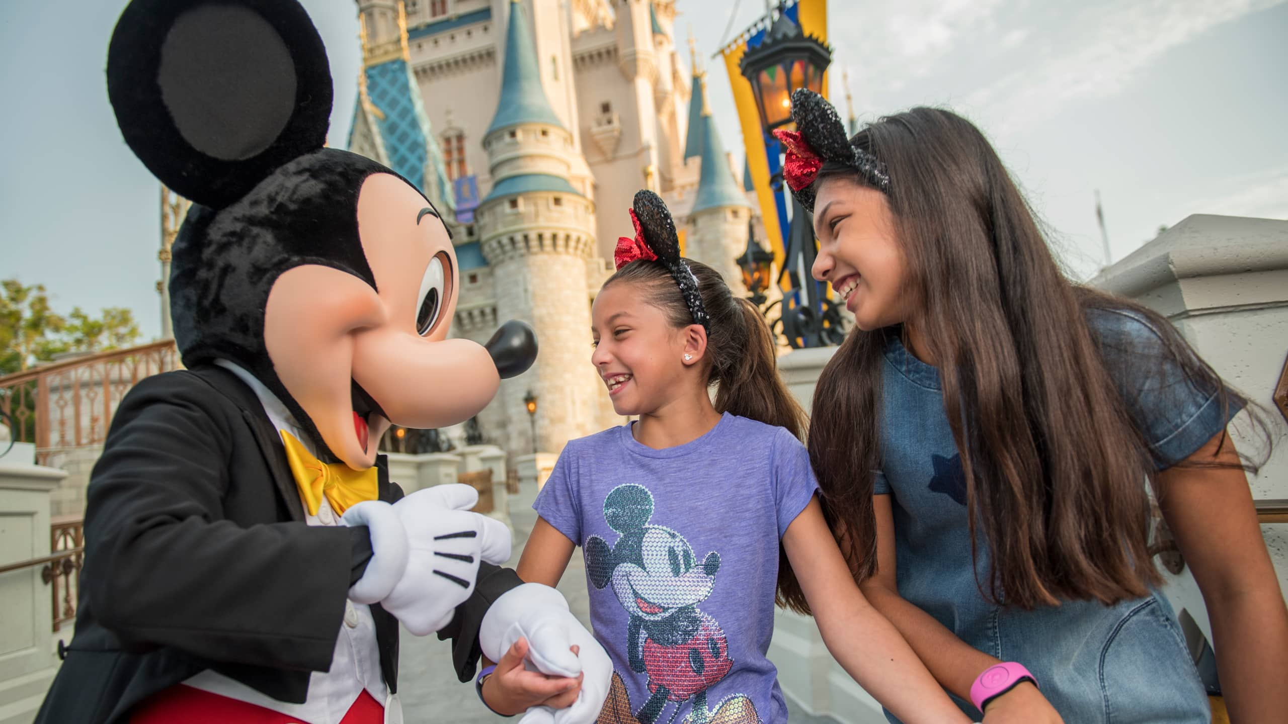 Mickey Mouse greeting 2 girls beside Cinderella Castle at Magic Kingdom park
