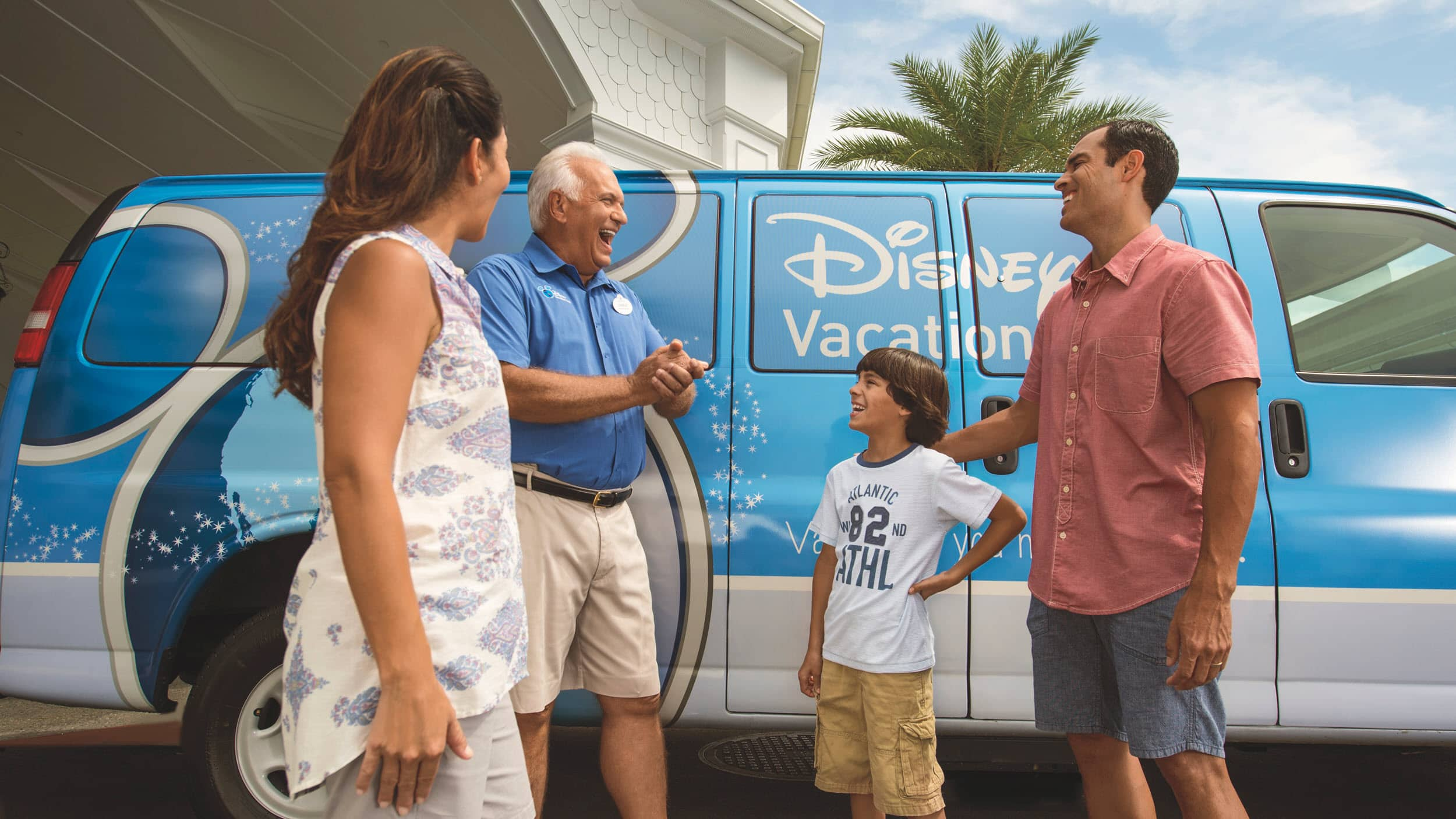 A Disney Cast Member talking to a man, woman and their son beside a Disney Vacation Club van