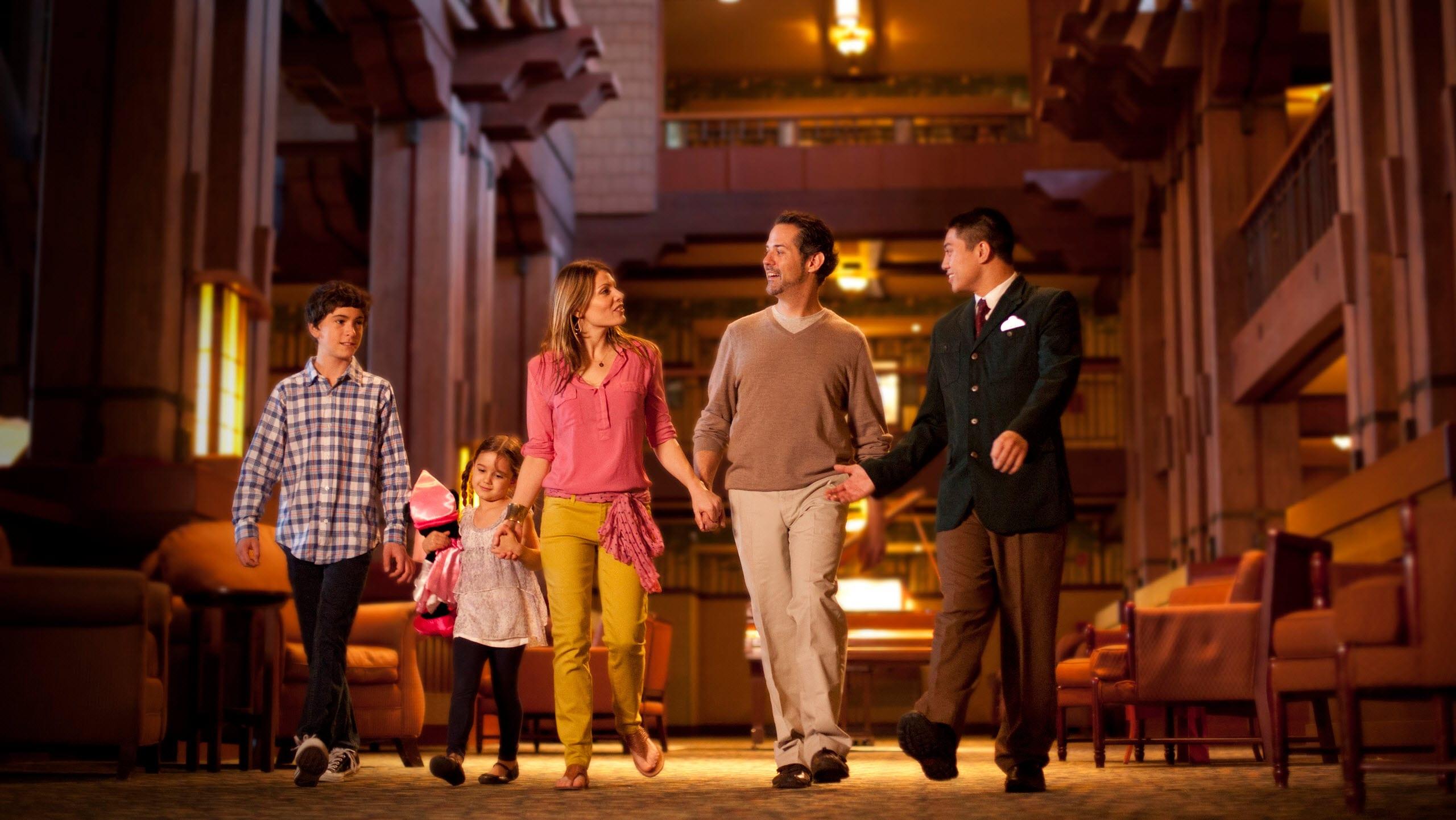 A Disney Cast Member leads a family of 4 through a hotel lobby