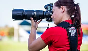 A photographer takes a photo on the field