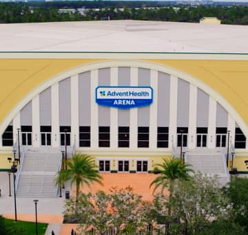 A walkway lined with palm trees leads to the entrance of the AdventHealth Arena at ESPN Wide World of Sports Complex
