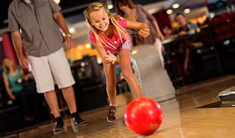 A smiling girl bowls at Splitsville Luxury Lanes while her dad watches in the background