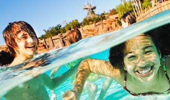 A boy stands in the Typhoon Lagoon Surf Pool and watches a girl swim underwater