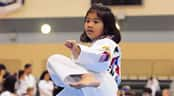 A girl in a gi performs a martial arts kick