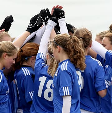 A soccer team of teenage girls huddle for a pre-game mass high-five