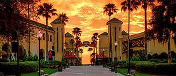 A palm tree and lamppost-lined concrete path leads to an archway with the ESPN Wide World of Sports Complex logo at sunset
